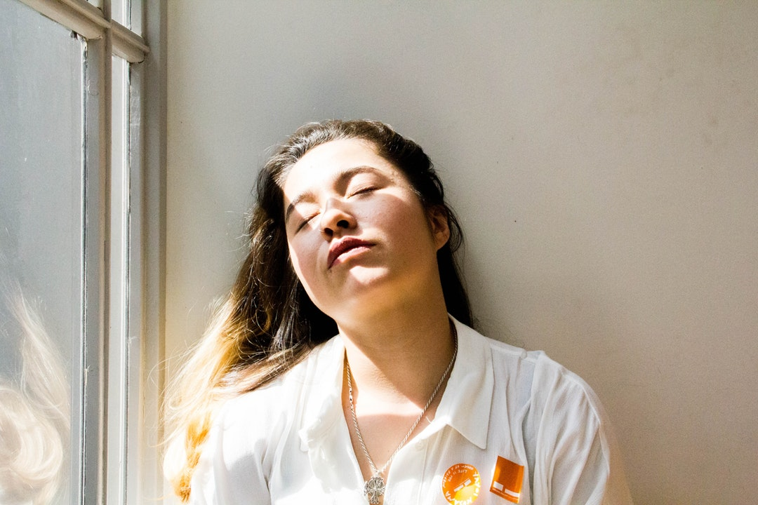 Tired woman wearing a uniform closes her eyes near a sunny window
