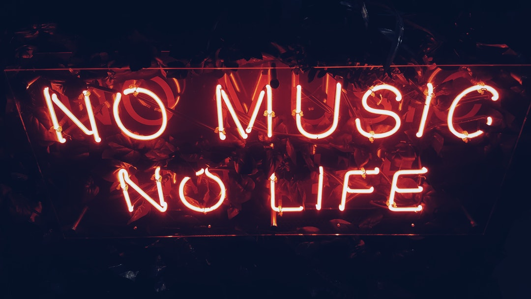 "A red neon reads ""No music, no life"" against a dark background"