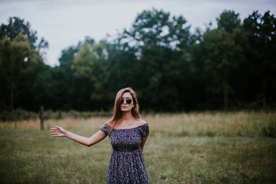 Woman in a dress standing in a field with her arm outstretched