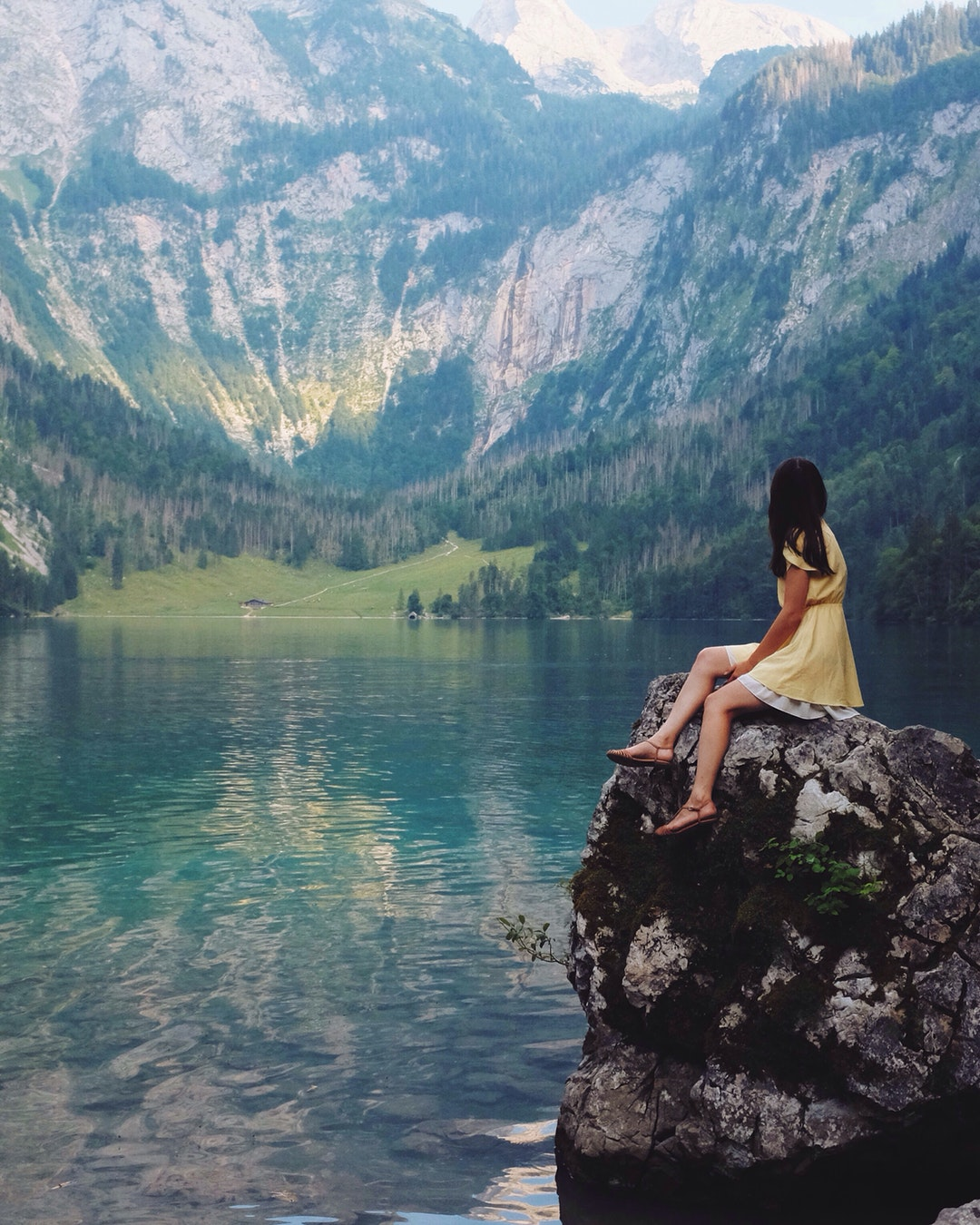 A woman in a yellow dress sitting on a large rock next to a lake and mountains in Шёнау-ам-Кёнигсзе, Бавария, Германия