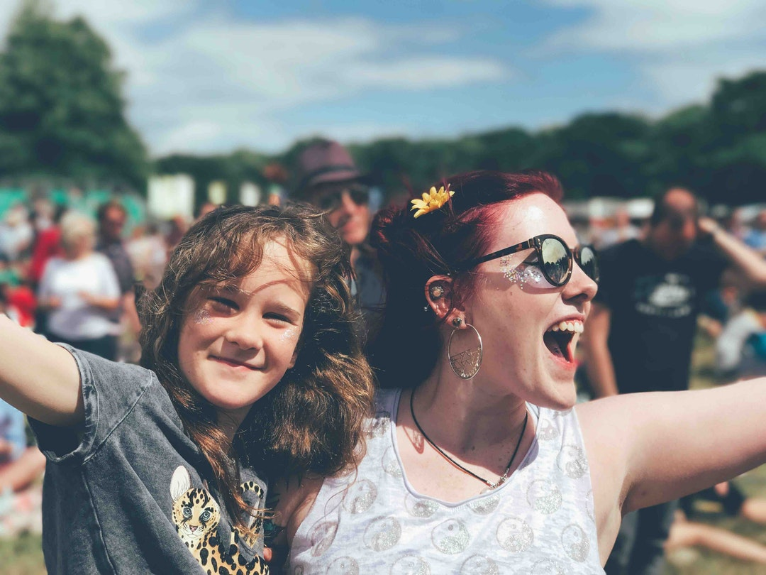 A woman and a girl cheering at a festival