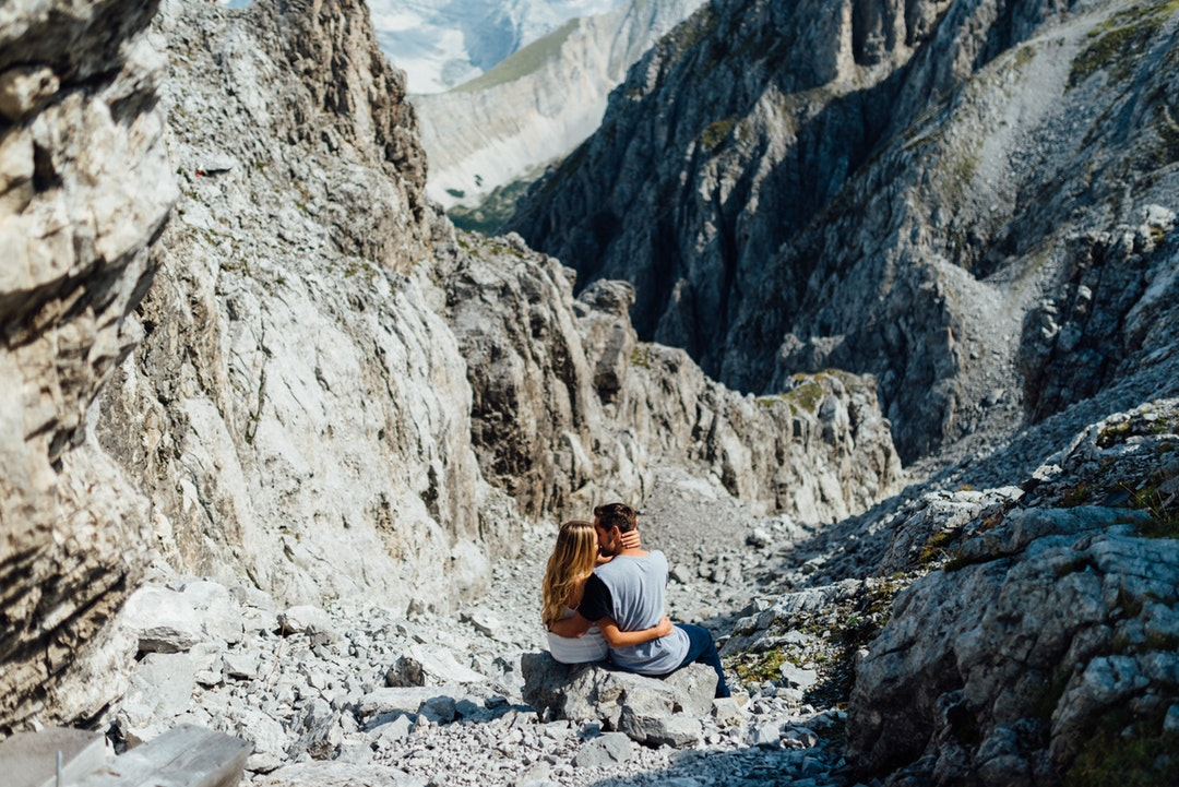 Couple embraces in a rocky mountain landscape