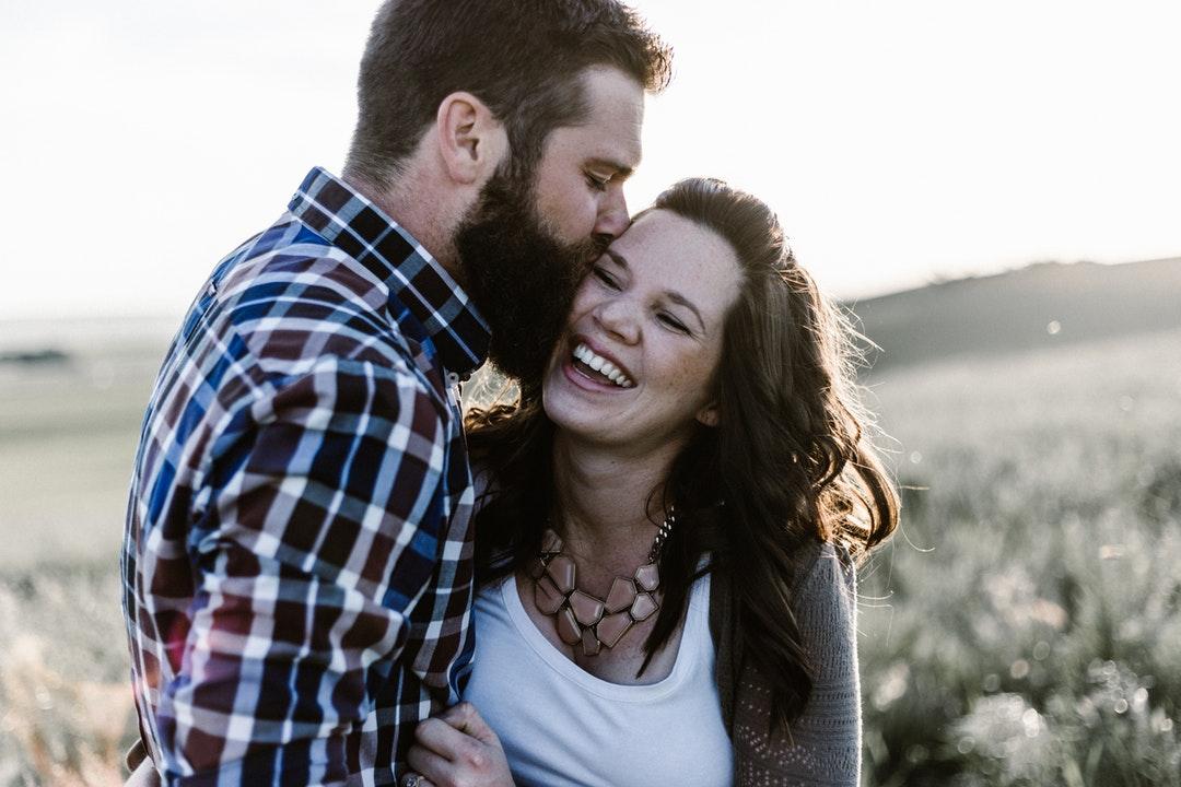 Boyfriend kissing his smiling happy girlfriend on the cheek