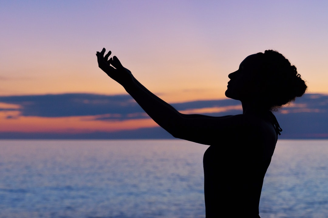 The silhouette of a woman doing yoga by the water during sunrise or sunset in Saint Joseph