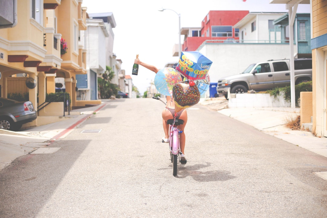 Woman driving a balloon decorated bicycle celebrating and holding a champagne bottle on the street at Hermosa Beach
