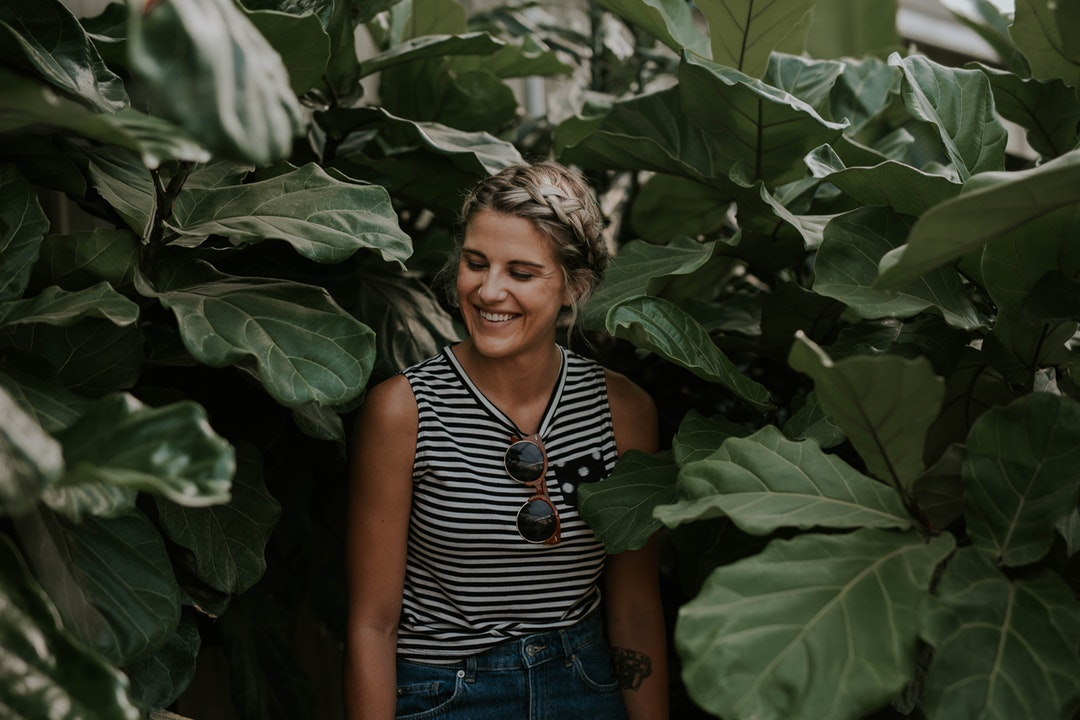 A woman in a tank top smiles with her eyes closed, standing among foliage