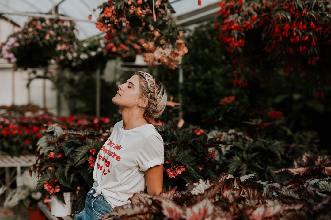 A woman with a braid closes her eyes with her head back in a botanical garden