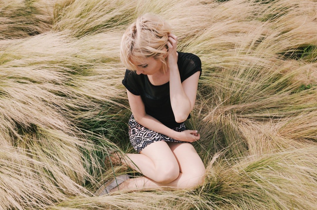 A blonde woman sitting in a field outside