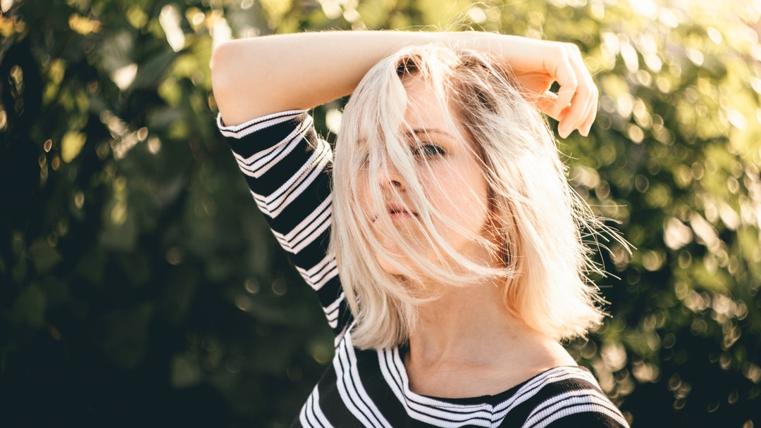 Woman with wind in her hair posing in a striped shirt