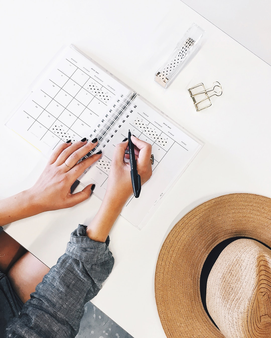 An overhead shot of a person writing in a planner on a desk