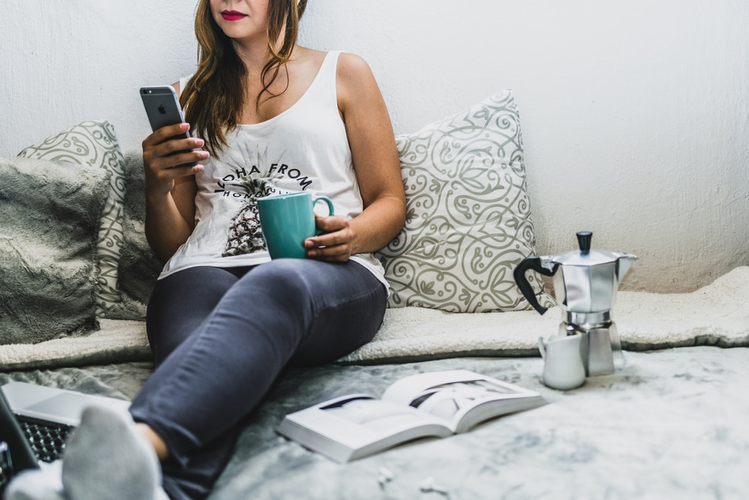 A woman sits on a bed with an open book, holding a mug and her cell phone