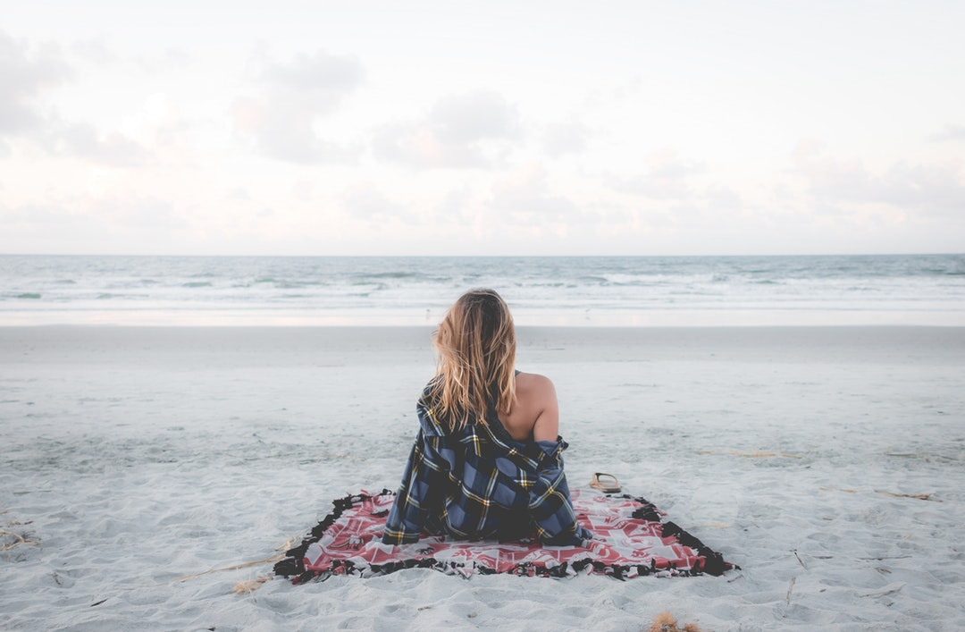 Young woman in checkered shirt sitting on a picnic blanket at the sand beach in Charleston