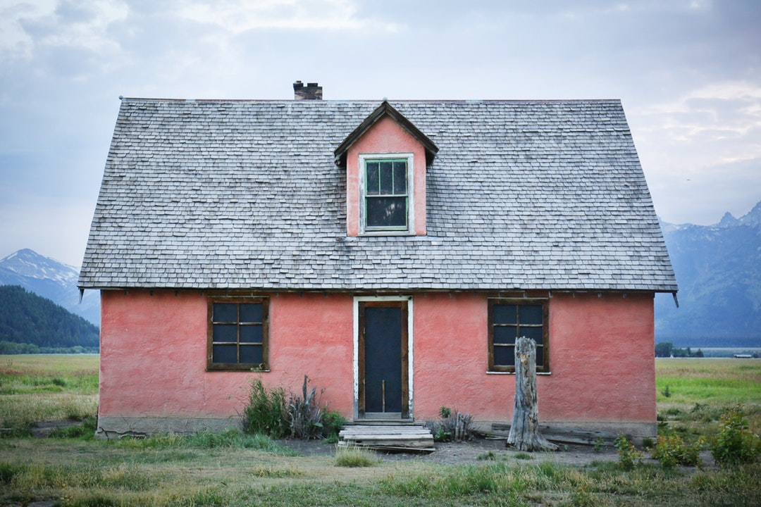 Small pink house with 3 windows in a grassy field with mountains in the background