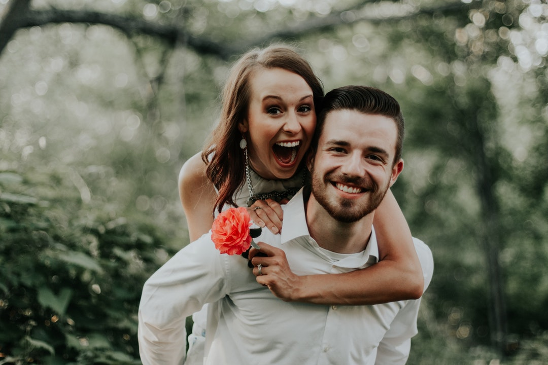 A smiling man gives his fiancee a piggyback ride as she holds a flower