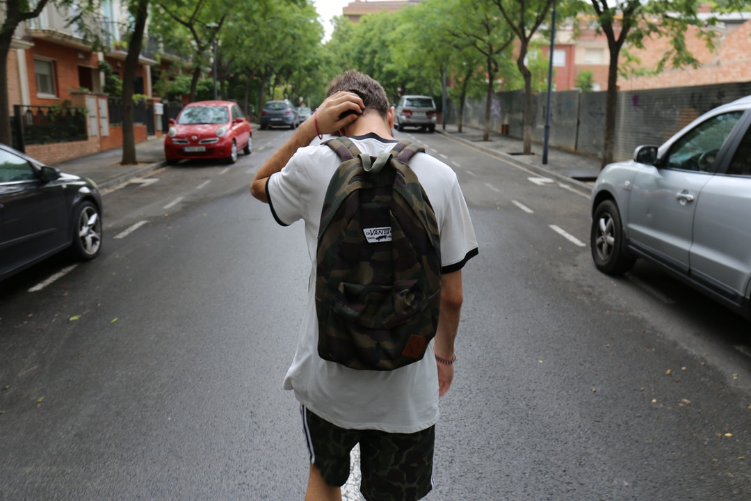 Teen boy walking home from school wearing a backpack