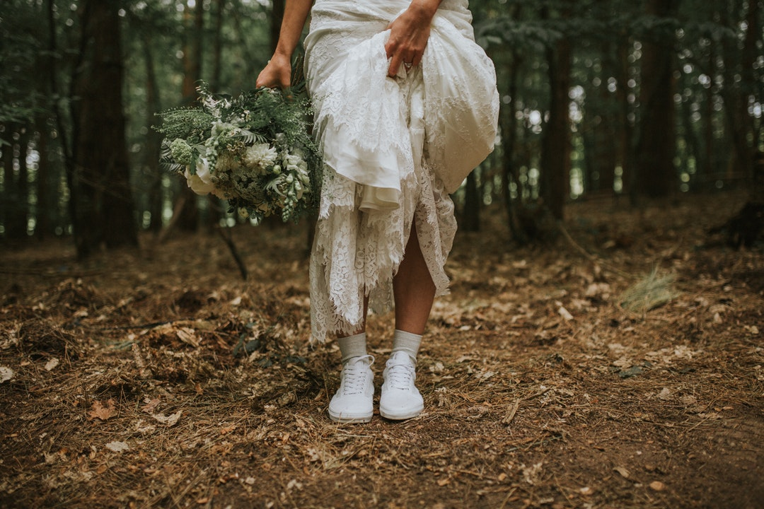 Bride in white tennis shoes holds up her wedding dress train and bouquet in the woods