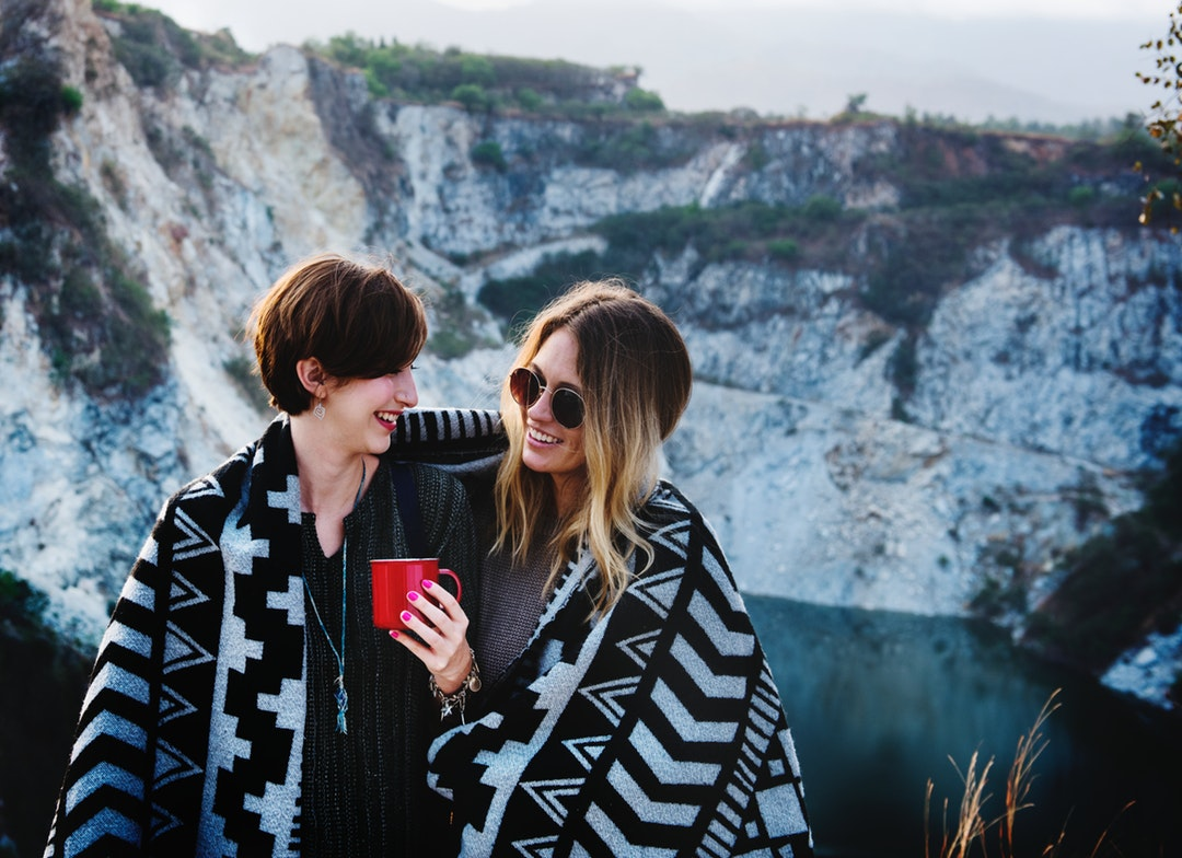 Two women stand closely, wrapped in a blanket, in front of a rocky landscape
