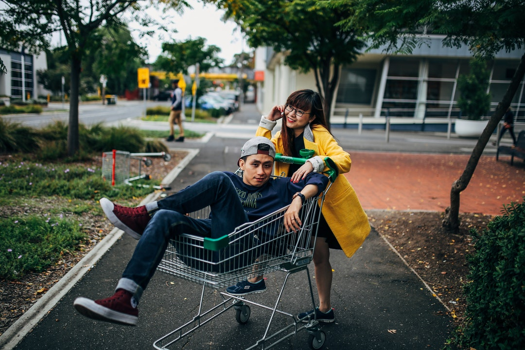 A woman leans onto a shopping cart, while a man poses inside on a city sidewalk
