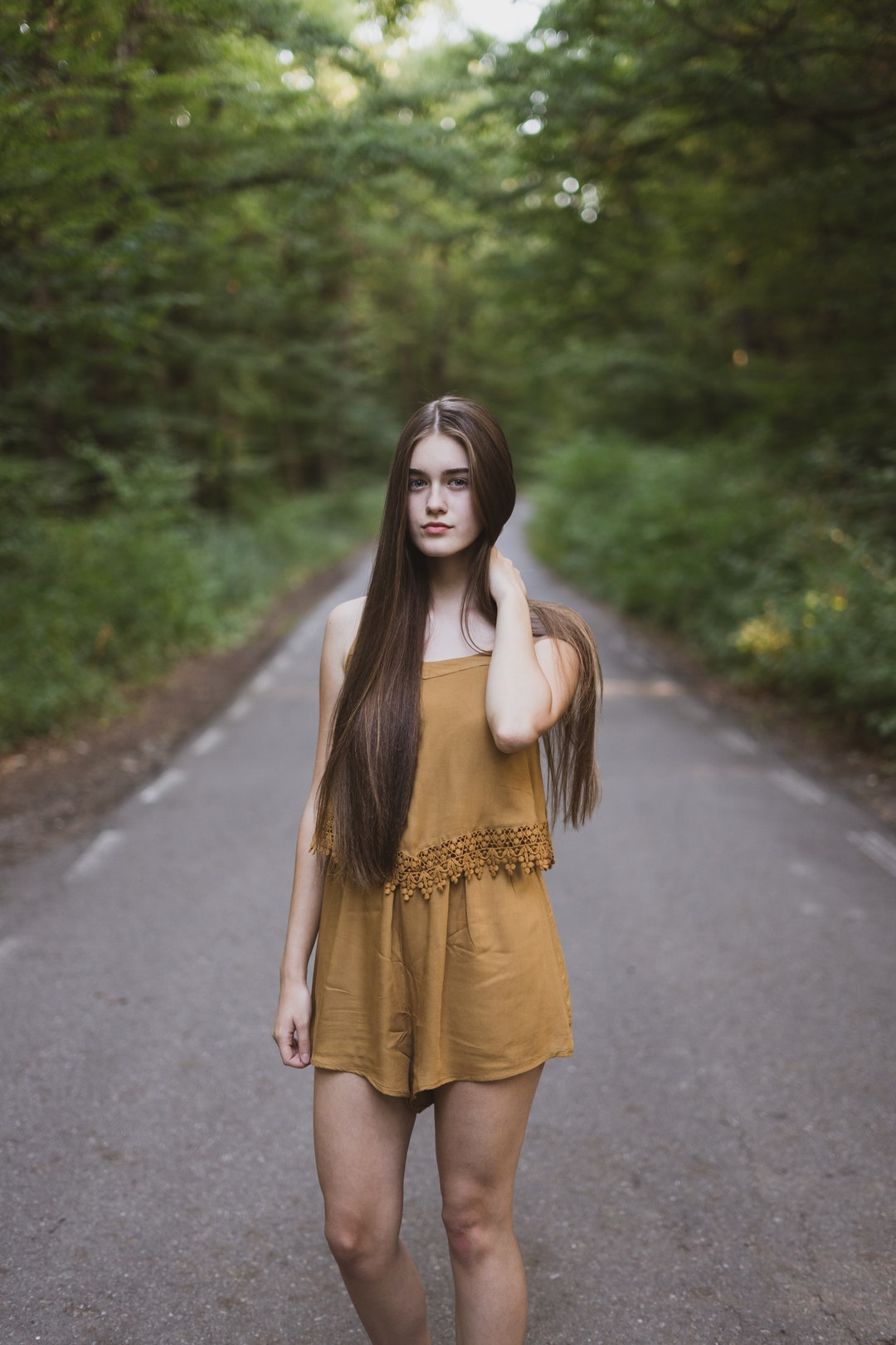 Woman with long hair in a yellow dress in the middle of a country road