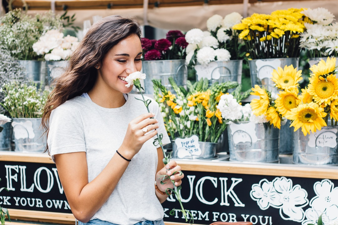 A woman at a floral stand in Nashville smiles while smelling a white flower