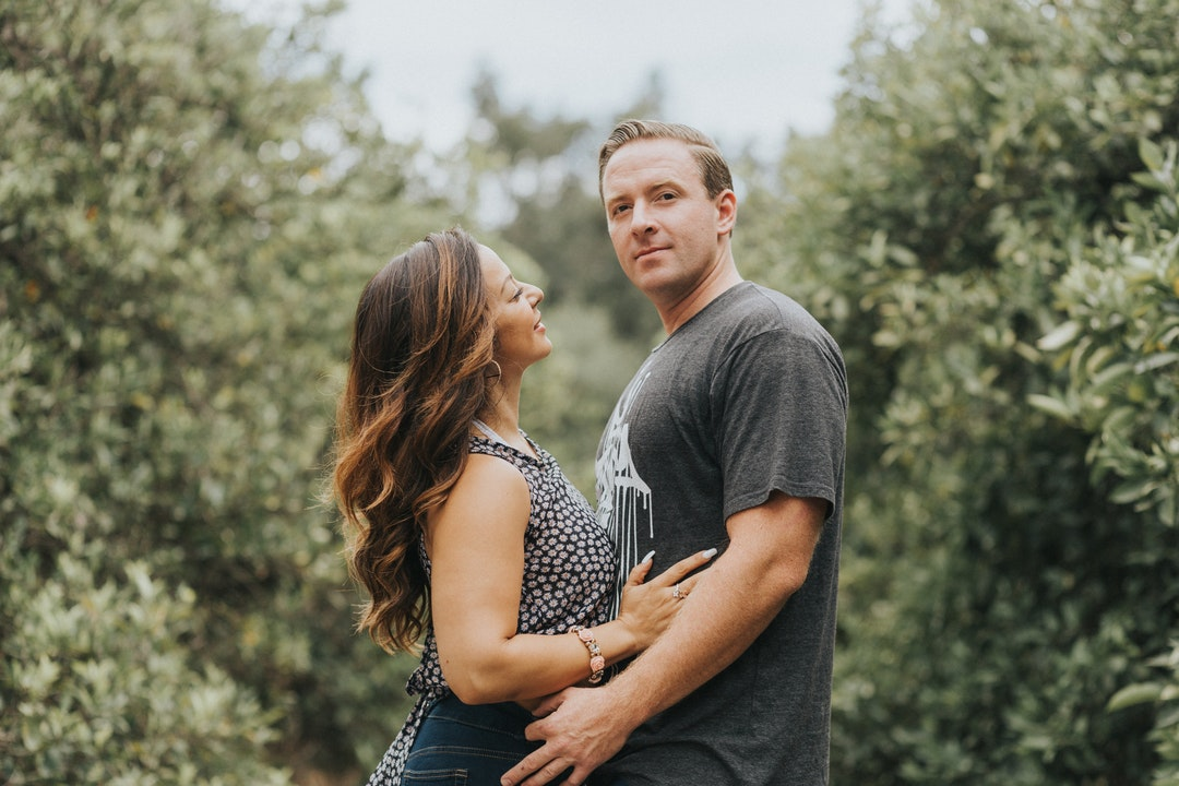 Happy couple embracing in a field of trees