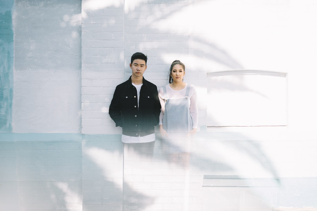 minimalist photography of man beside woman while leaning against wall