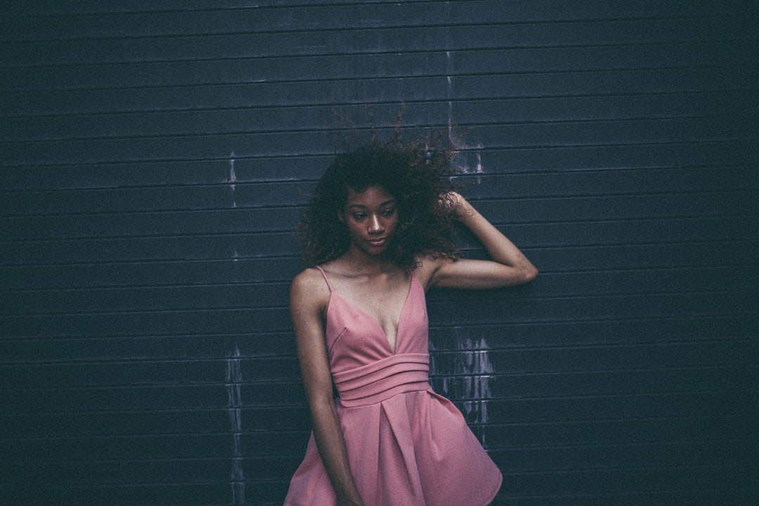 Woman in a pink cocktail dress looks unsure posed against a garage door
