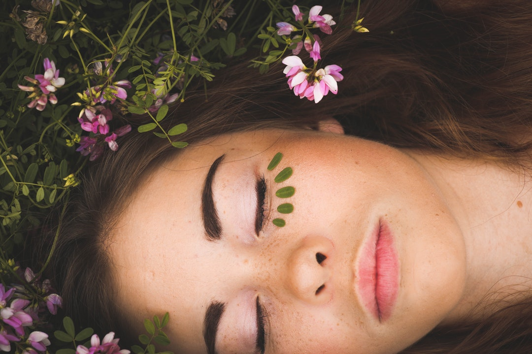 A woman lying on the ground with her eyes closed, wearing makeup under her eyes.