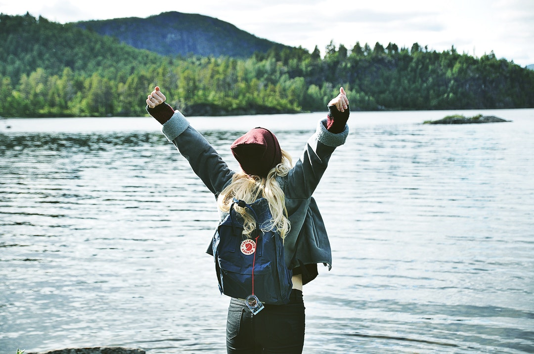 A backpacking woman stretching her arms up while looking out into the lake.
