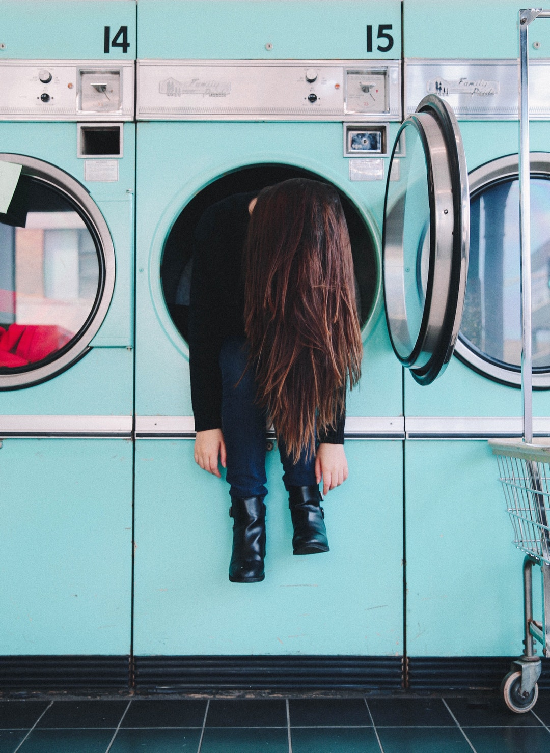A person hanging out of a dryer at a laundromat.