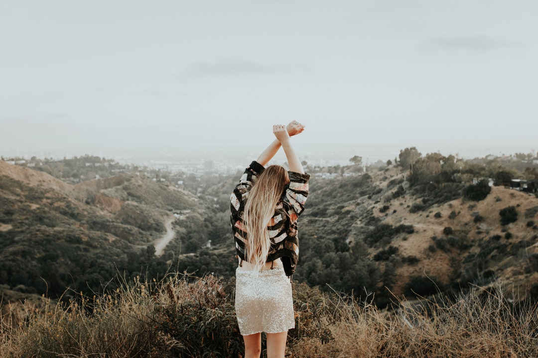 A woman holding her arms up in the sky on top of a mountain.