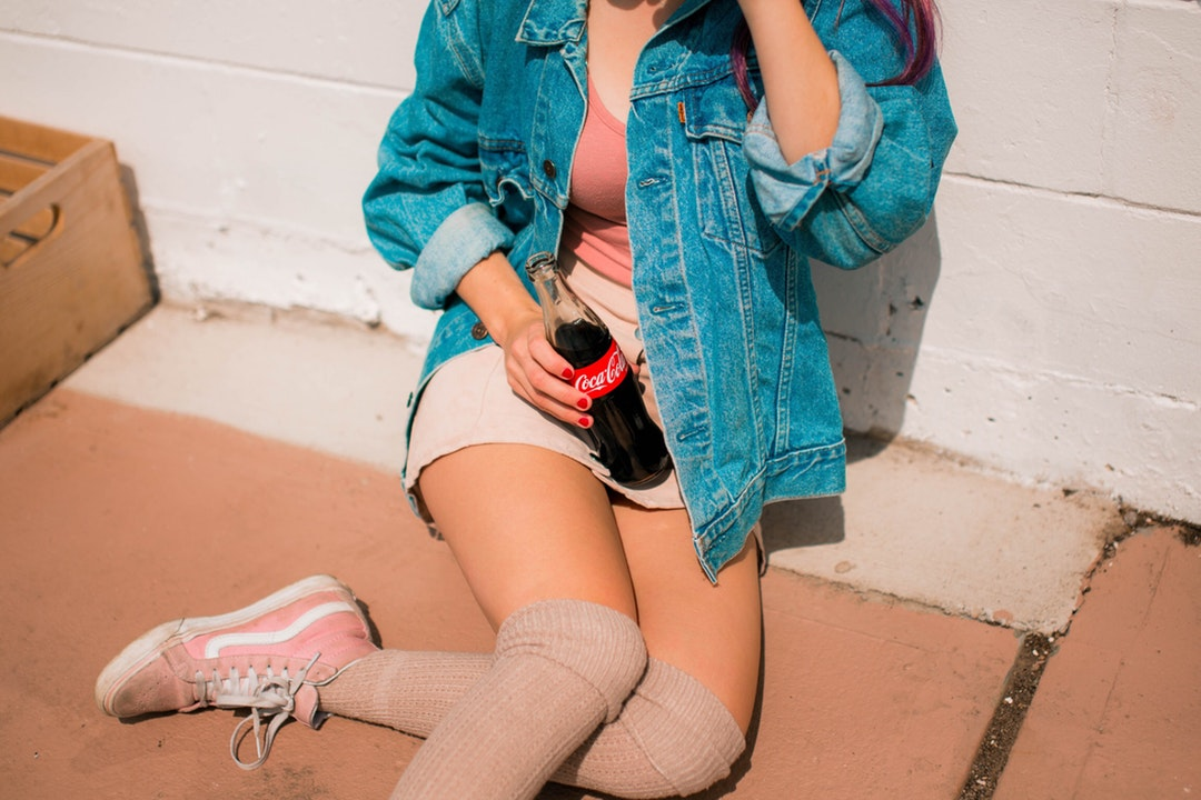 A woman wearing a denim jacket sitting on the ground while drinking a glass bottle of Coca Cola.
