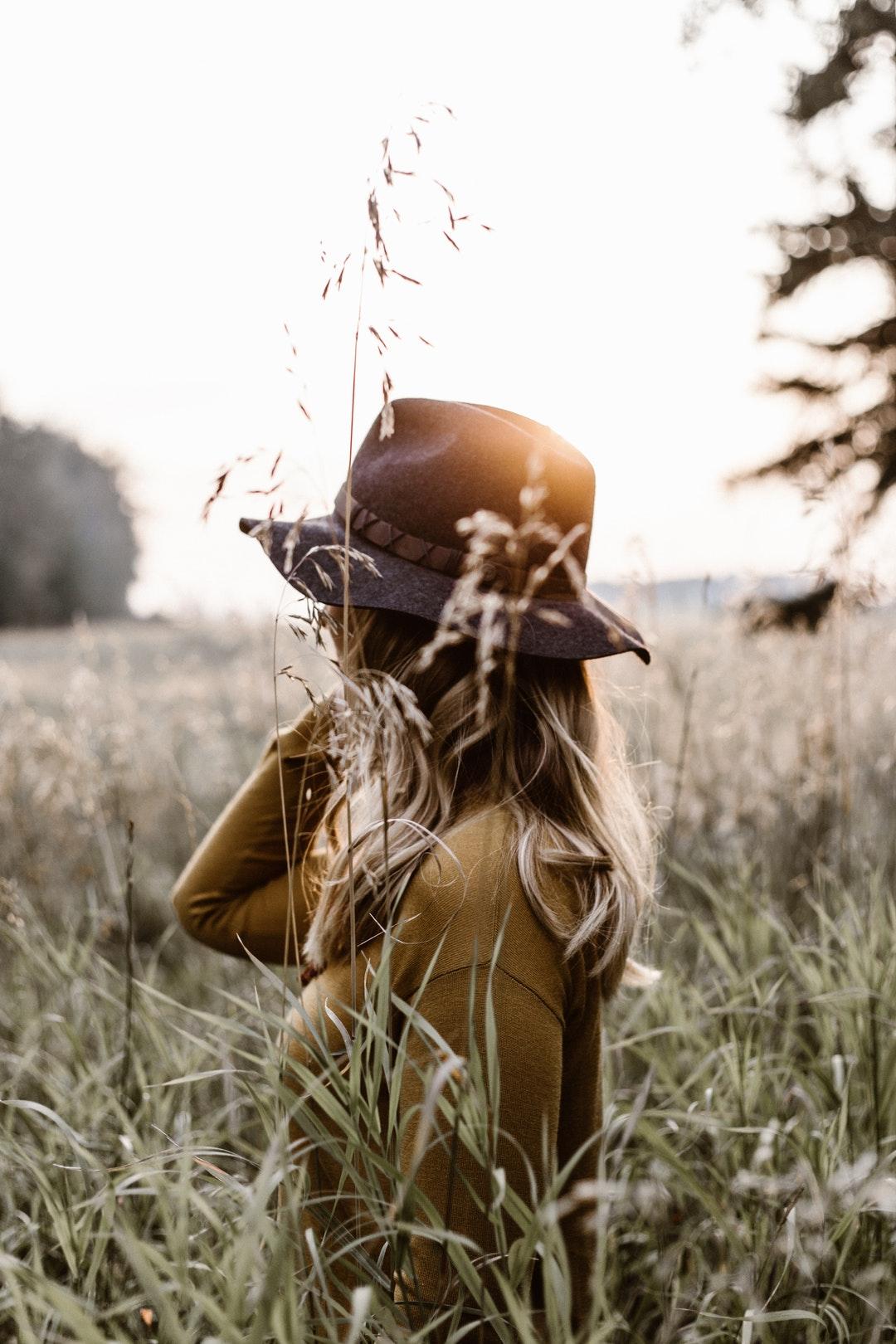 A hat wearing woman in a tall field.