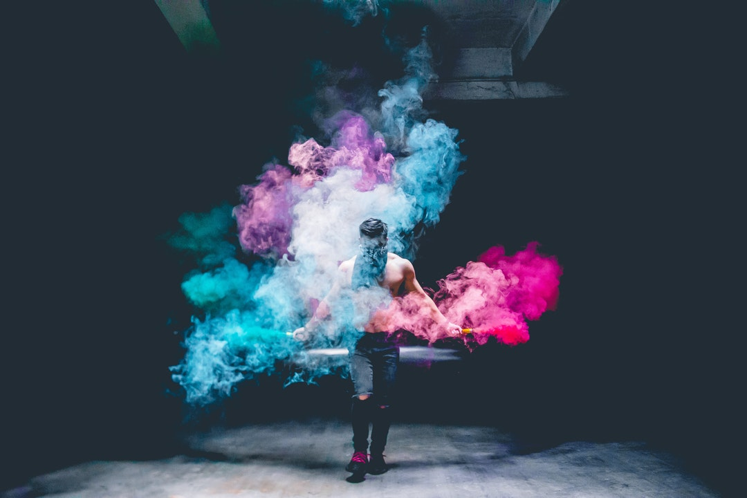 woman in black jeans surrounded with colored powders