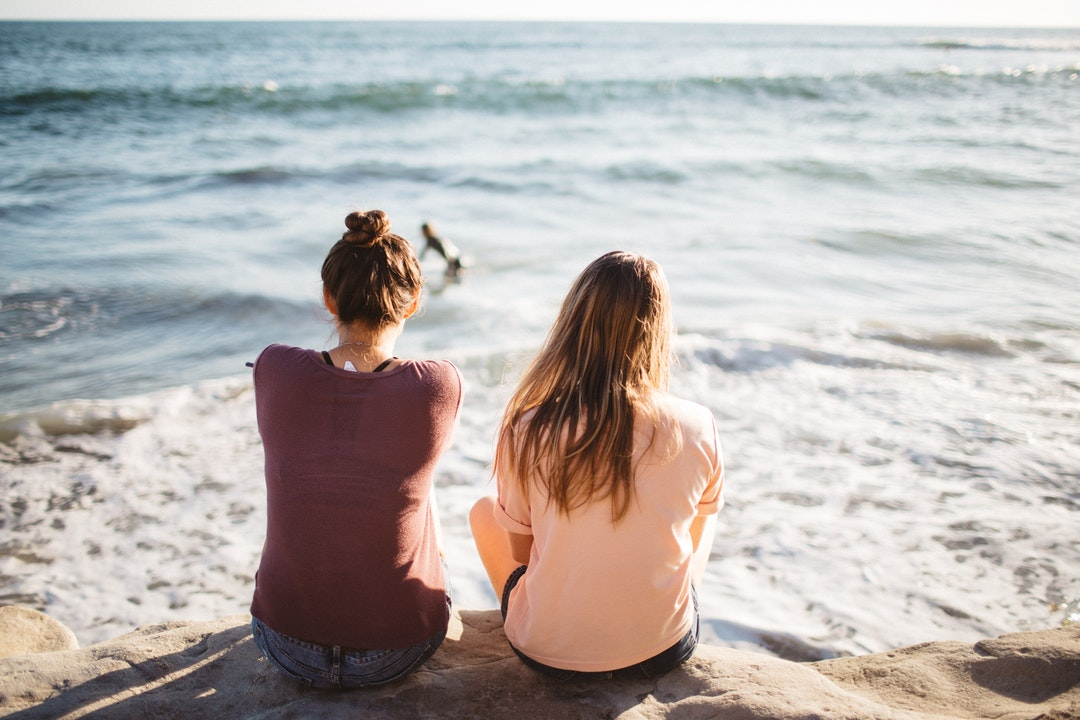 two women sitting on cliff looking at the ocean