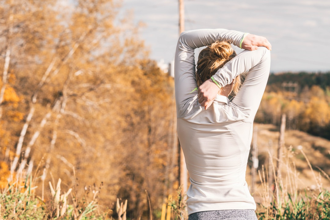 woman standing while stretching beside brown leafed trees