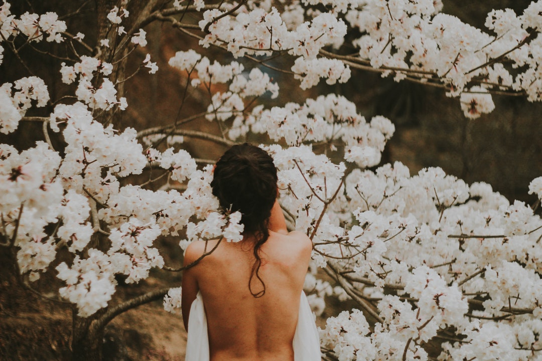 topless person standing near white petaled flowers
