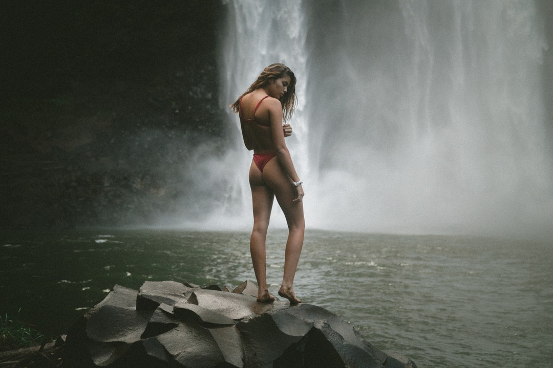 woman in red panty and bra standing of black stone near waterfalls