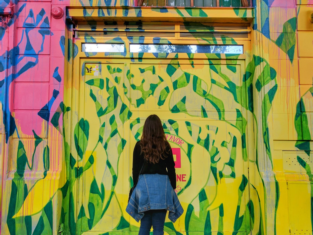woman in front of multicolored wall