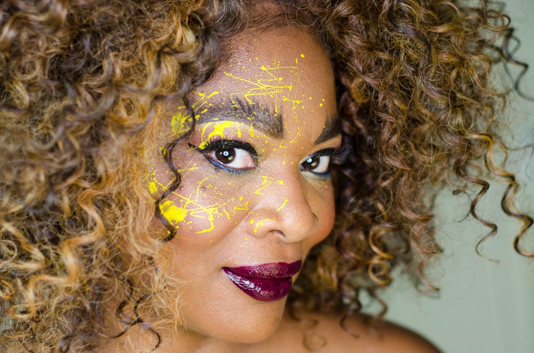 kinky haired woman smiling wearing red lipstick with yellow face paint