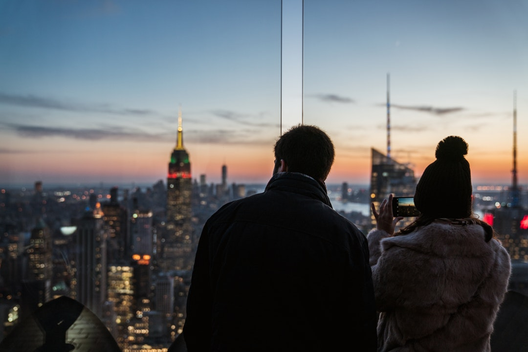 man and woman taking photo on high-rise buildings