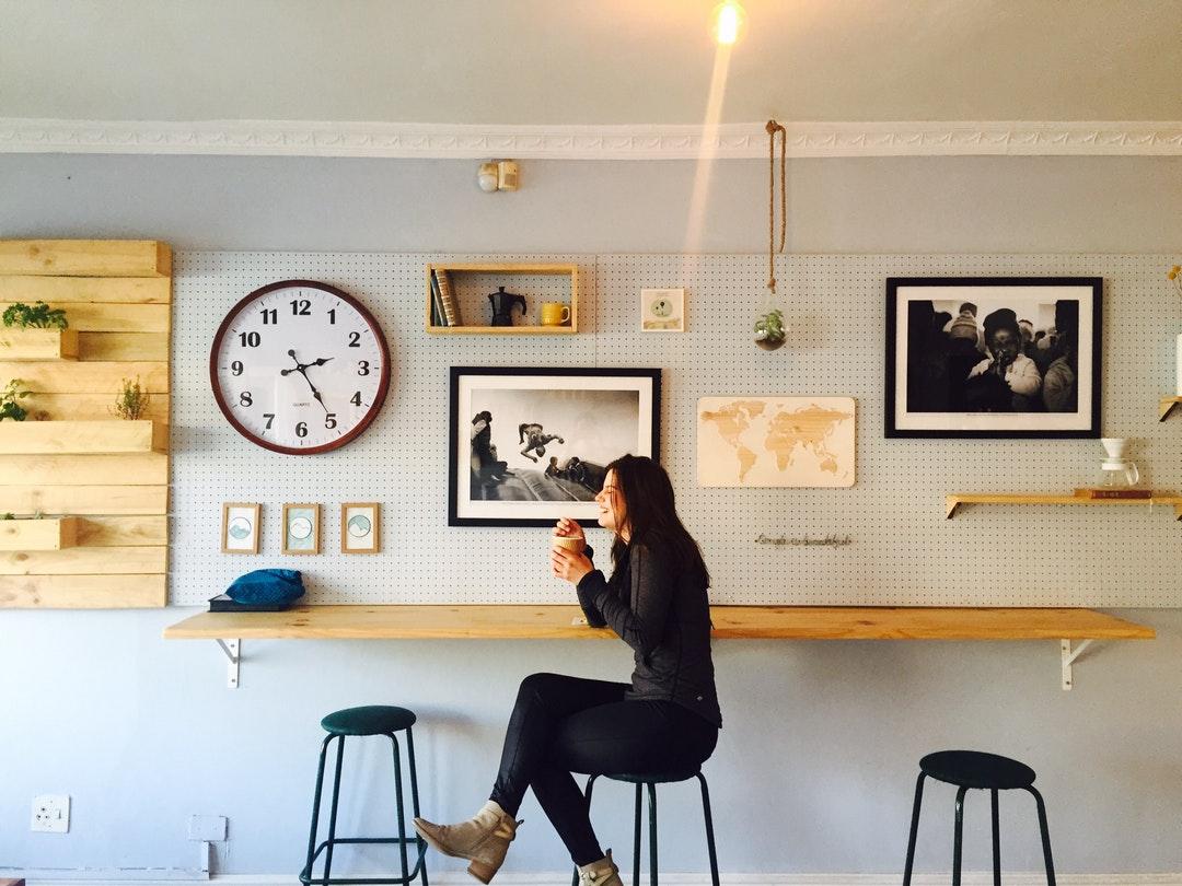 woman sitting on stall near wall mounted desk