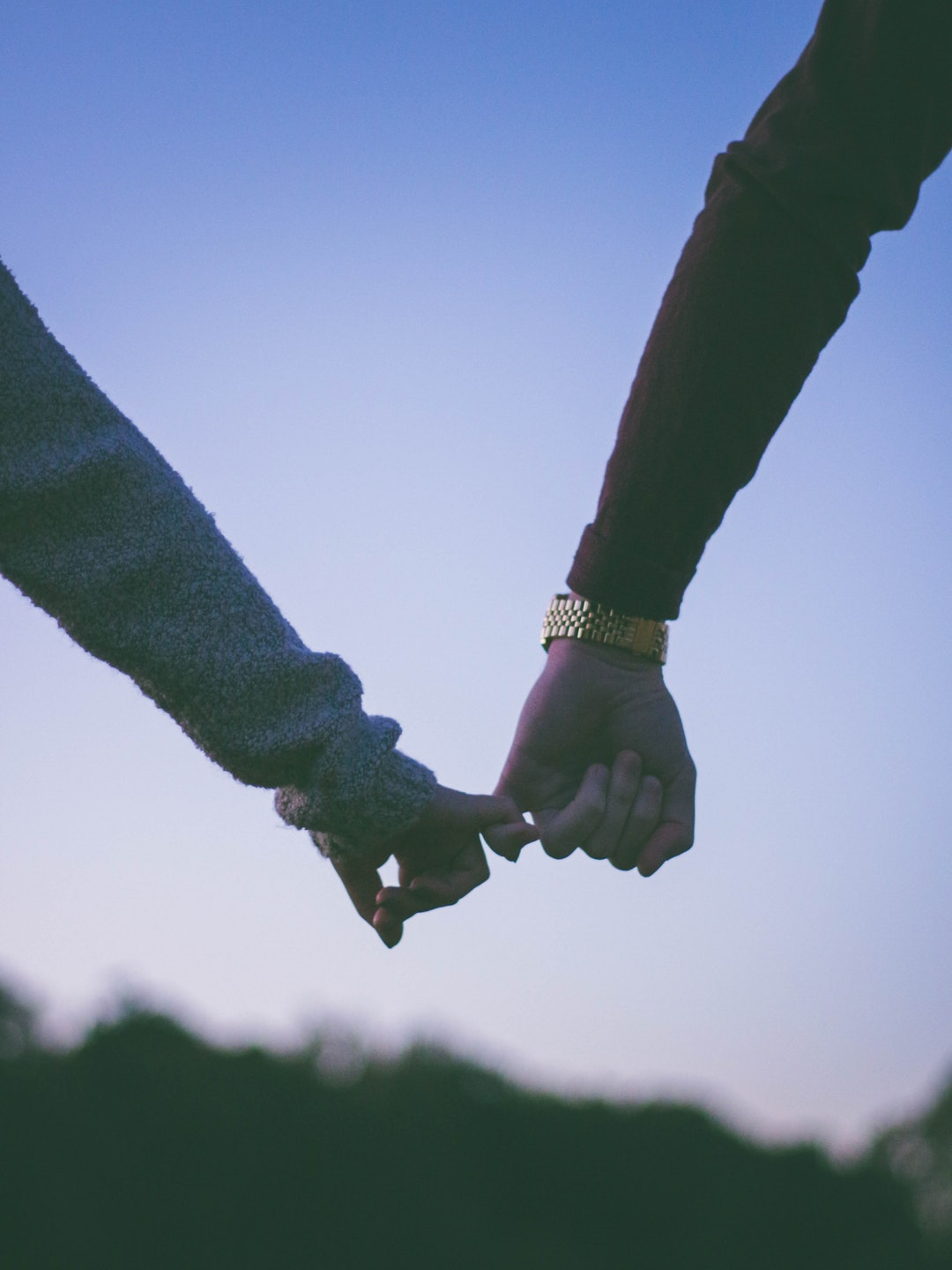 man and woman holding hand using pinky fingers