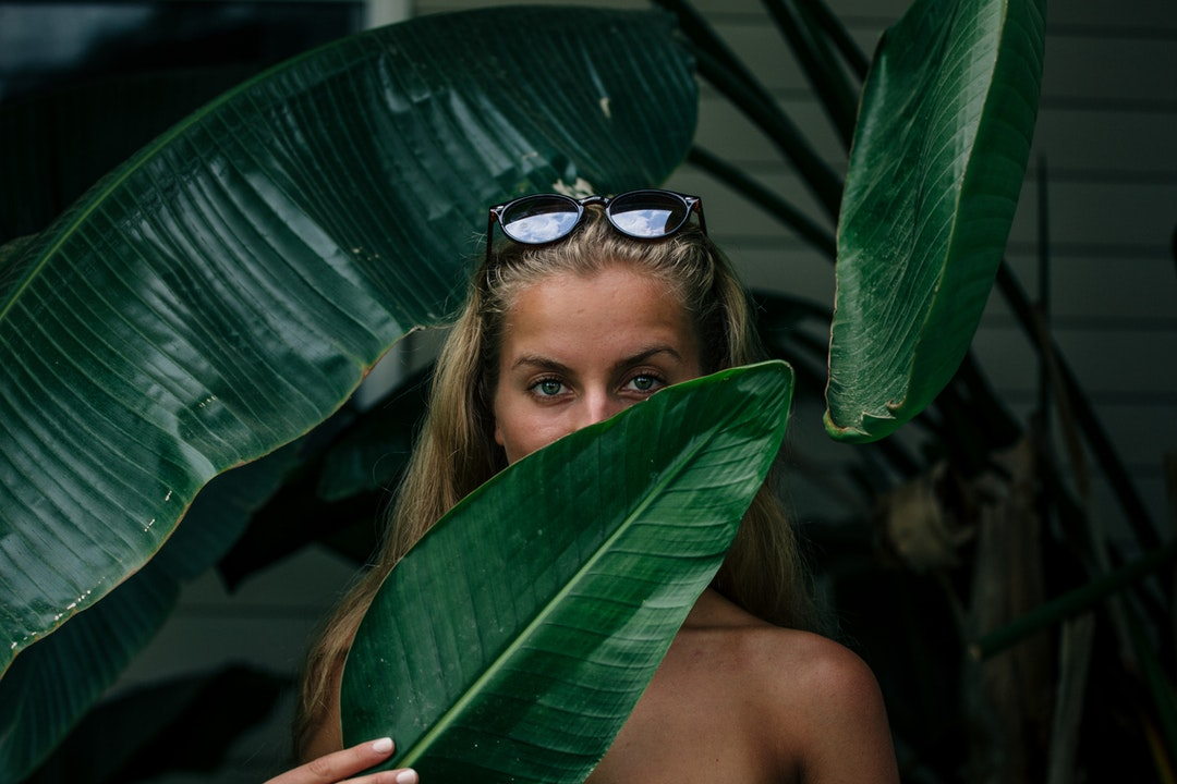 woman covering her face with green leaf