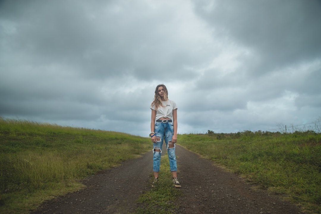 woman standing on dirt road under cloudy sky during daytime