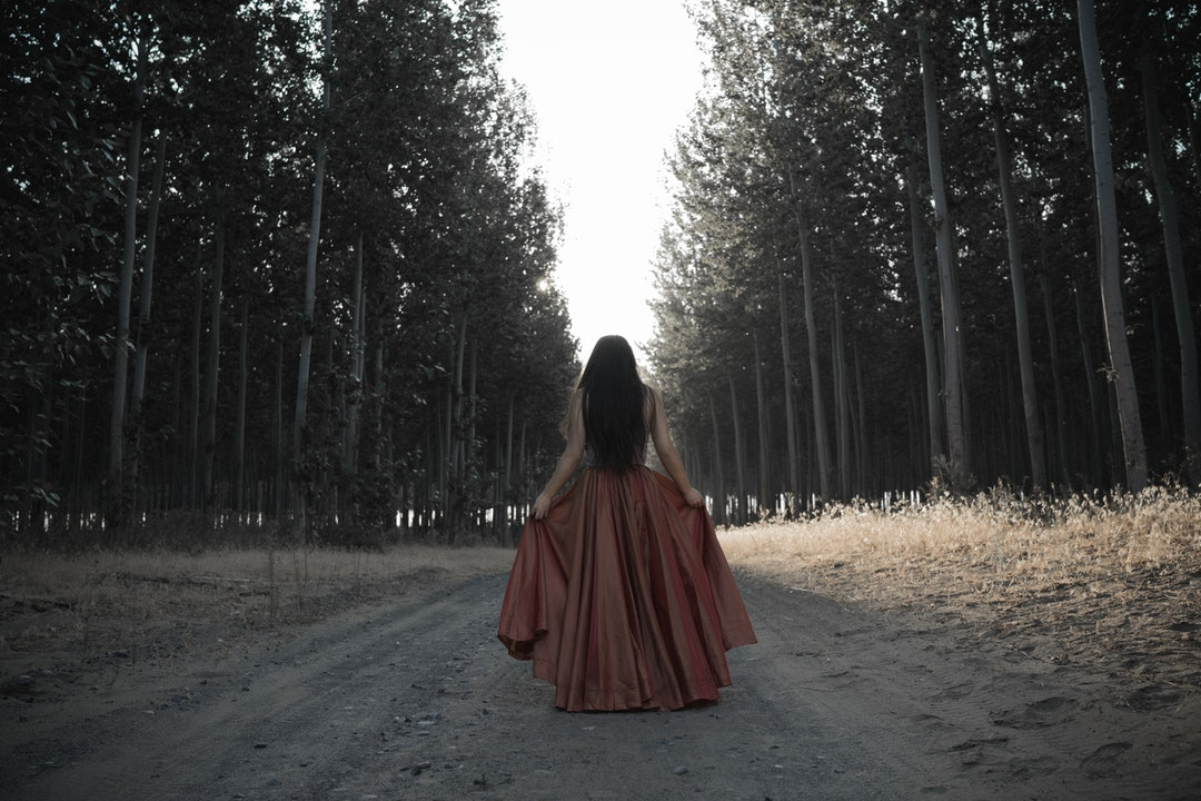 woman holding her brown dress in the middle of forest