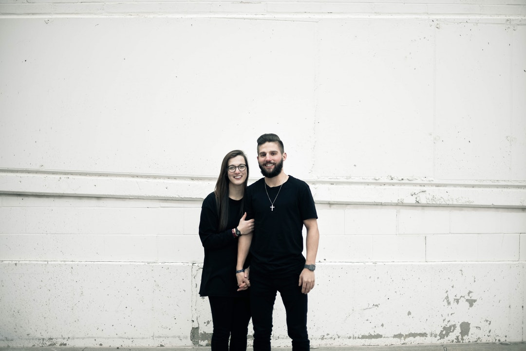 couple standing in front of white concrete wall