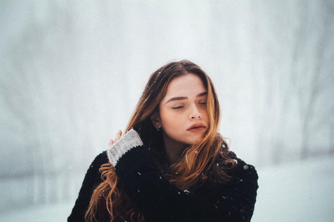 woman wearing black coat holding her hair