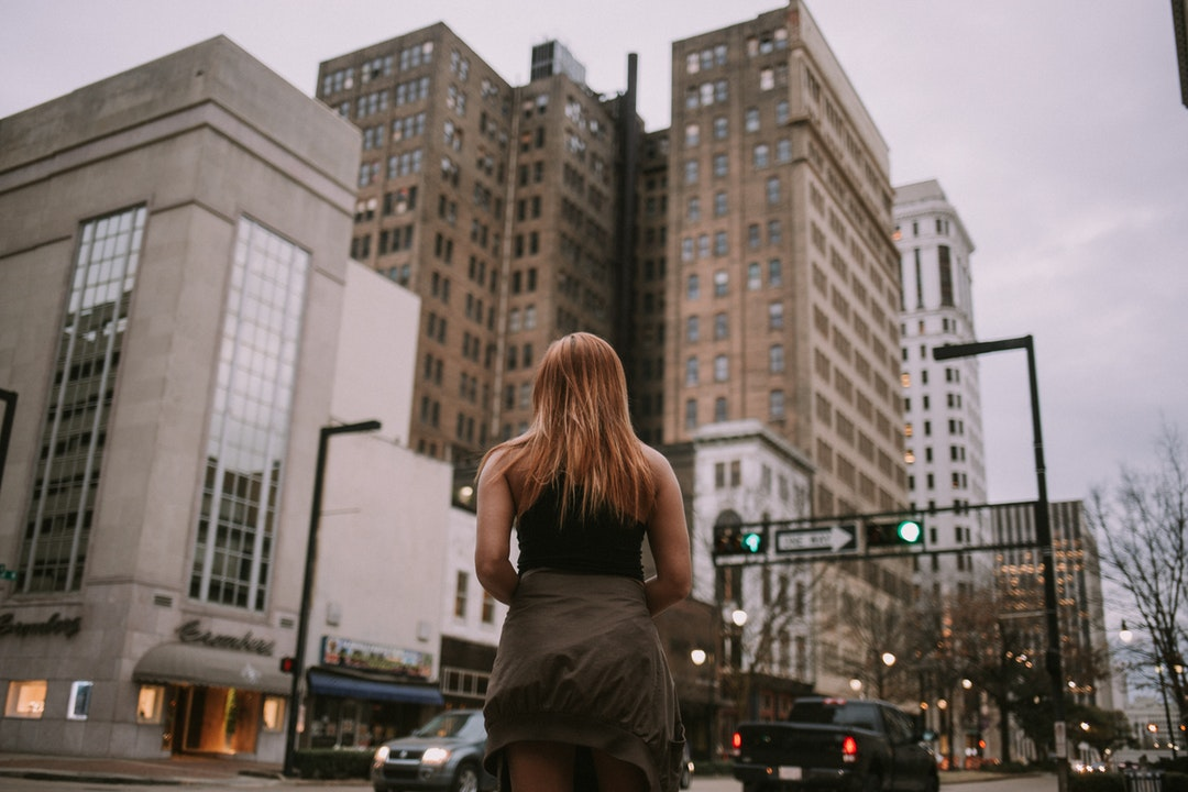 woman standing near cars and concrete building during daytime