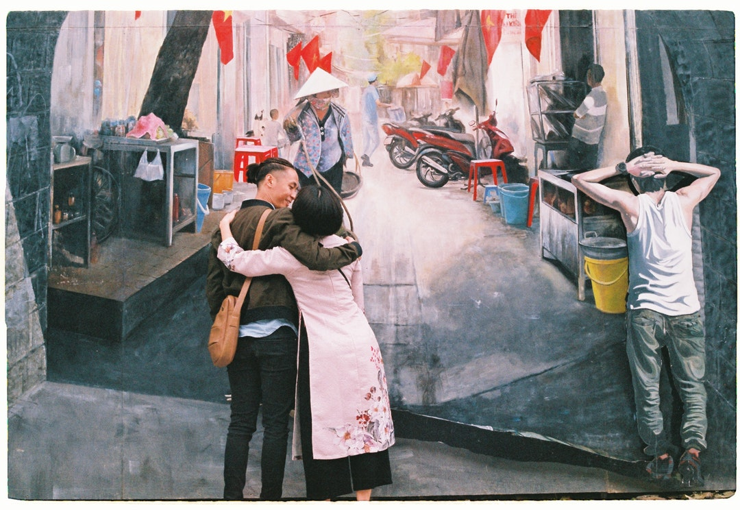 photo of man and woman hugging each other front of wall art